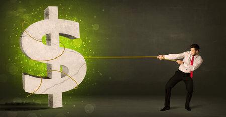 competici�n: Hombre de negocios que tira de un gran signo de d�lar concepto verde sobre fondo Foto de archivo