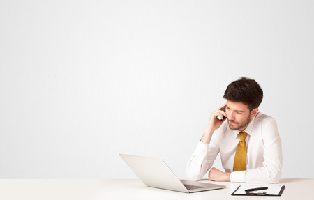 successful business: Business man sitting at white table with a white laptop on white background