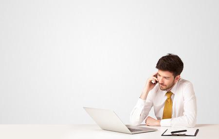 Man writing: Hombre de negocios sentado en la mesa blanca con una computadora port�til en blanco sobre fondo blanco