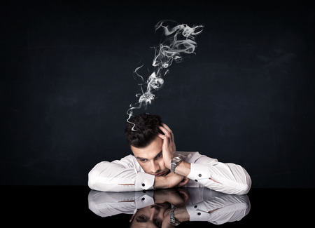 unmotivated: Young depressed businessman sitting with smoking head