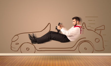 Happy man driving an hand drawn car on the wall concept photo