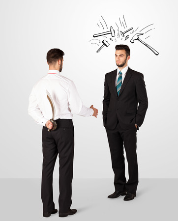 ruthless: Ruthless businessman hiding a weapon white drawn beating hammer marks Stock Photo