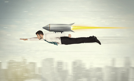 engine fire: Superhero business man flying with jet pack rocket above the city concept Stock Photo