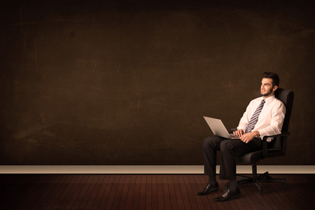 Businessman holding high tech laptop on brown background with copyspace photo