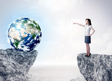 bridging: Businesswoman standing on the edge of mountain with a globe on the other side Stock Photo