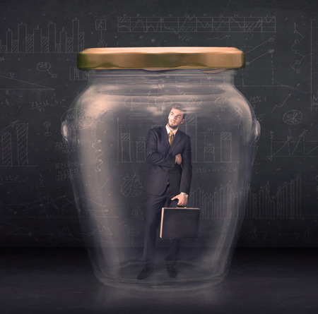 imprisoned: Business man closed into a glass jar concept on background