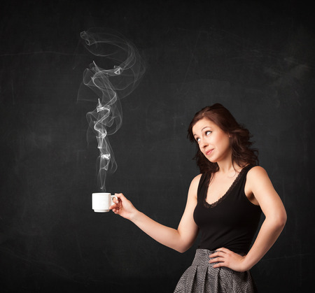 steamy: Businesswoman standing and holding a white steamy cup on a black background