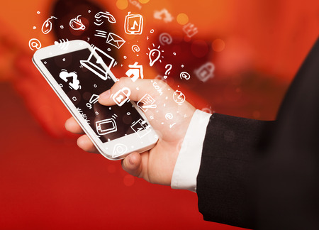 Hand holding smartphone with media icons and symbol collection photo