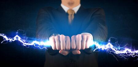 blue lightning: Business man holding electricity light bolt in his hands concept