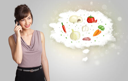 nutrition: Pretty woman presenting a cloud of healthy nutritional vegetables concept Stock Photo