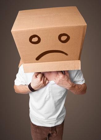 cara triste: Hombre joven de pie con una caja de cart�n marr�n en la cabeza con cara triste