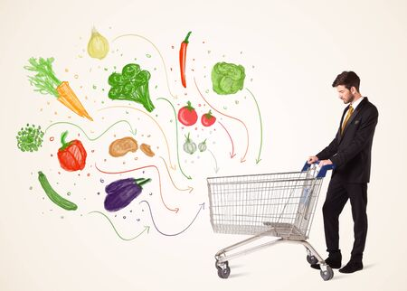 shopping carriage: Businessman pushing a shopping cart and healthy vegetables coming out of it Stock Photo