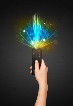 changing channel: Hand holding a remote control, shining and explosive signal coming out of it