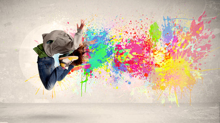 Happy teenager jumping with colorful ink splatter on urban concept photo