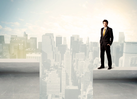 bridging: Businessman standing on the edge of rooftop with city  Stock Photo