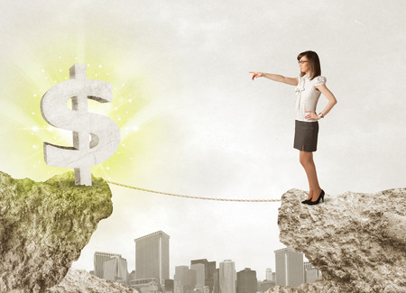 bridging the gap: Businesswoman standing on the edge of mountain with a shining dollar mark on the other side