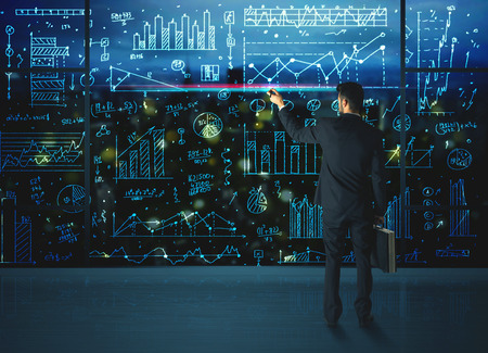 stock market data: Businessman drawing business statistics on glass wall