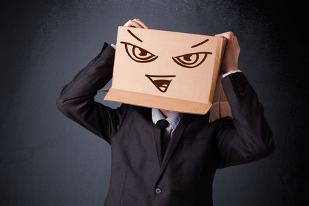sad face: Businessman standing and gesturing with a cardboard box on his head with evil face