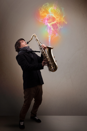 comming: Attractive young musician playing on saxophone with colorful abstract fume comming out