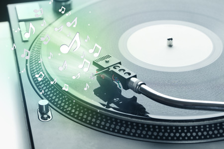 Turntable playing music with audio notes glowing concept on background photo