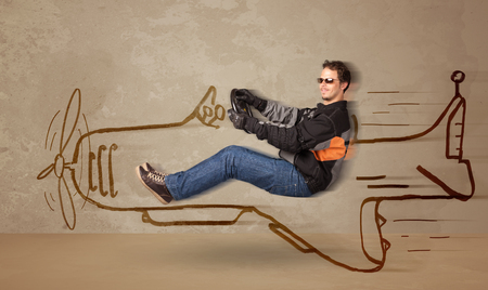 levitate: Funny pilot driving a hand drawn airplane on the wall concept