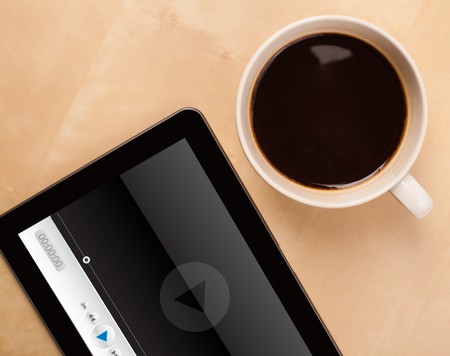 video screen: Workplace with tablet pc showing media player and a cup of coffee on a wooden work table close-up