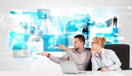 tecnolog�a informatica: Las personas de negocios en el escritorio con im�genes de tecnolog�a azules modernos en el fondo Foto de archivo