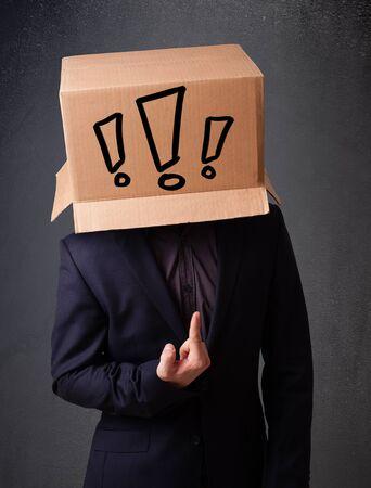 point exclamation: Jeune homme debout et gesticulant avec une bo�te en carton sur la t�te avec un point d'exclamation Banque d'images