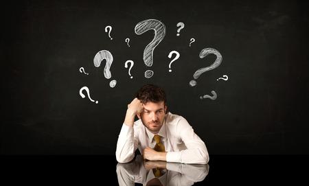 indecisive: Depressed businessman sitting under question marks