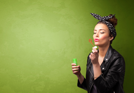 blowing bubbles: Beautiful woman blowing soap bubble on copyspace green background