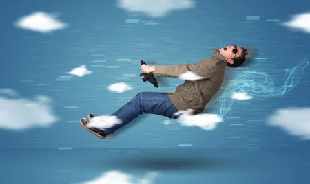 Racedriver divertido joven de conducción entre nubes concepto sobre fondo azul