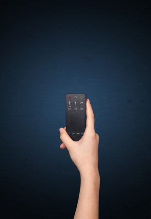 changing channel: Hand holding a remote control on blue background