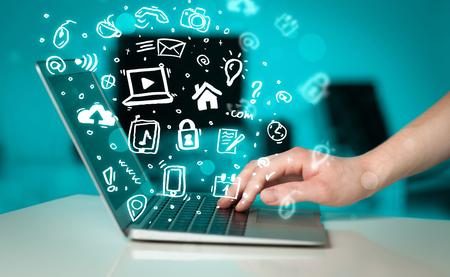 � writing: Escritura de la mano en la computadora port�til con iconos y s�mbolos de los medios de comunicaci�n comming fuera