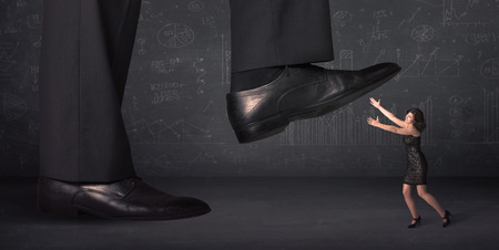 beg: Huge leg stepping on a tiny businnesswoman concept on background Stock Photo