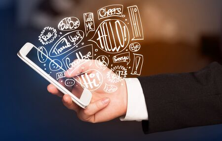handheld device: Hand holding phone with hand drawn speech bubbles concept Stock Photo
