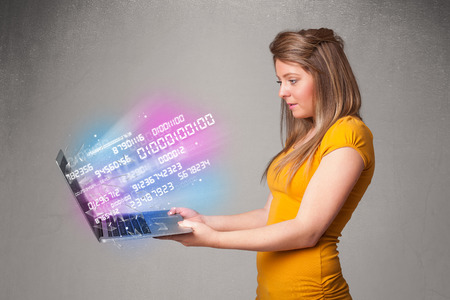 encode: Attractive casual woman holding laptop with exploding data and numers