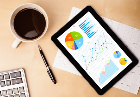 growth chart: Workplace with tablet pc showing charts and a cup of coffee on a wooden work table close-up
