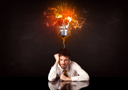 smithereens: Depressed businessman sitting under a blowing idea bulb
