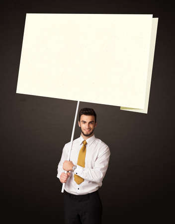 Young businessman holding a big, white paper photo