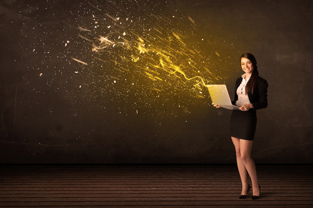 Businesswoman with laptop and energy explosion on background concept photo