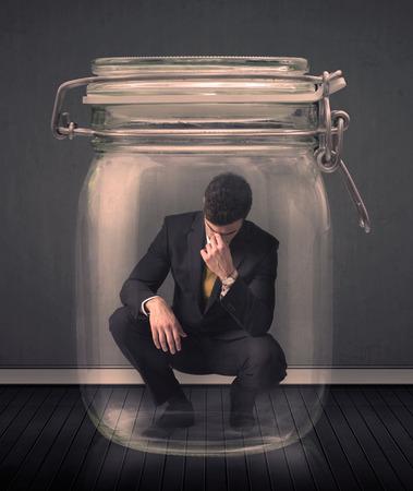 suffocating: Businessman intrappolato in un concetto di vaso di vetro su sfondo