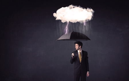 rainy day: Businessman standing with umbrella and little storm cloud concept on background