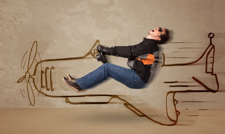 Funny pilot driving a hand drawn airplane on the wall concept photo
