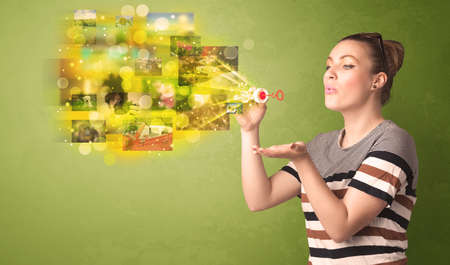 lips glow: Cute girl blowing colourful glowing memory picture concept on green background