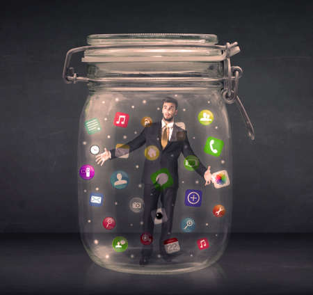 captured: Businessman captured in a glass jar with colourful app icons concept on background