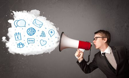 shouting: Young man shouting into loudspeaker and modern blue icons and symbols come out Stock Photo