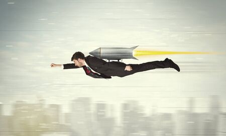 Superhero business man flying with jet pack rocket above the city concept photo