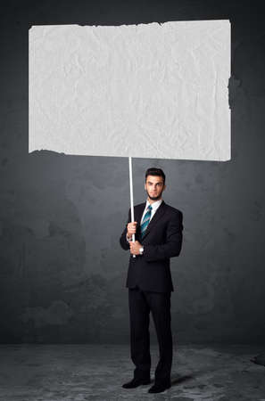 Young businessman holding a big blank booklet paper photo