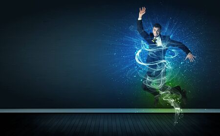 Talented cheerful businessman jumping with glowing energy lines on background Stock Photo