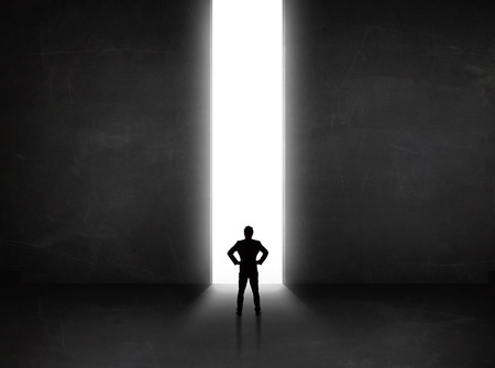 person looking: Business person looking at wall with light tunnel opening concept